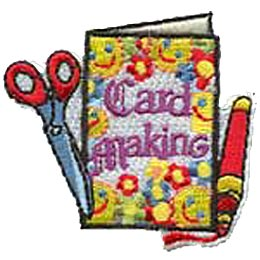 A flower and smiley face decorated card is displayed with the words ''Card Making'' on it. A marker lays next to the card on the right and scissors slightly lay on top of the card to the left.