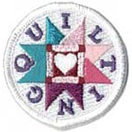 This round, white, merrow bordered patch has a white heart inside a square frame and surrounded by a starburst pattern. The word ''Quilting'' is formed with each individual letter placed inside the recess of the starburst pattern.
