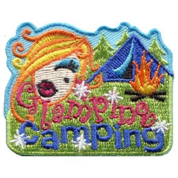 The head of a young woman with perfect hair and a made-up face floats beside a tent and a campfire. Underneath, the words 'Glamping Camping' are embroidered amidst sparkles.