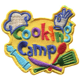 Colourful letters spell out the text, 'Cooking' which sits above of the word 'Camp'. A chef's hat is perched on top of the letter 'C' in 'Cooking'. Underneath the text, from left to right, is a pepper grinder, a knife, a spatula, and a spoon. In the top right, over the letter 'n' in 'Cooking,' is a white gloved hand with the pointer finger and thumb curling to connect tip-to-tip (giving the OK sign).