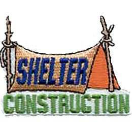 A rope is tied near the top of two vertical branches that form the poles for a tent. A blanket is draped over the rope to create the tent itself. The word ''Shelter'' is written on the makeshift tent and ''Construction'' is embroidered in green underneath.