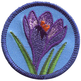 <p>This round badge displays a purple crocus flower opening up in bloom. Three strands of grass poke up from the bottom of the patch, reaching towards the top.</p>