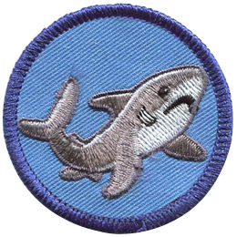 This round badge displays a grey shark in a curved 'U' position with it's tail on the left and head on the right.