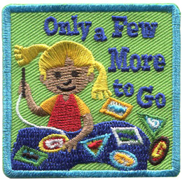 A young girl sews patches and crests onto a navy blue blanket. There are three patches sitting off to the side that haven't been sewed onto the blanket yet. Text on the crest reads, 'Only a Few More to Go.'