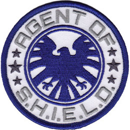 This circular patch forms the logo of the Agents of S.H.I.E.L.D. In the center is a blue eagle with its wings spread wide. Around the top curve of the patch are the words 'Agents of' and the bottom curve has 'S.H.I.E.L.D.'
