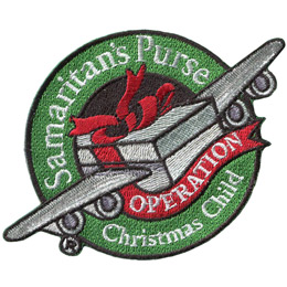 From the center outwards, this patch displays a shoe box tied closed with a red ribbon and with two airplane wings. The gift box is coming out of a green ring with the text 'Samaritan's Purse' at the top of the hoop and 'Christmas Child' embroidered at the bottom. A red, ribbon comes off the shoebox and forms a banner under the plane. This banner reads 'Operation' on it. This is Samaritan's Purse's Operation Christmas Child patch.