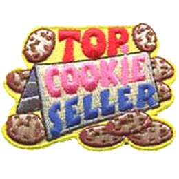 A folded piece of paper displays the words ''Cookie Seller.'' Above the sign the word ''Top'' is surrounded by a cookie on either side. Other cookies lay scattered around the sign.