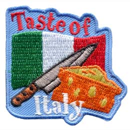 The green, white, and red vertical stripped Italian flag waves in the background as a sharp knife and a wedge of cheese are overlapped on top of it. The words ''Taste of'' are embroidered at the top of the flag and ''Italy'' is written near the bottom of the patch.