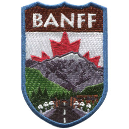 This emblem has the name 'Banff' at the top on a brown background. Just below it, front and center, is a paved road lined with lights leading to Banff itself. A green forest, complete with a waterfall and a towering snow-capped mountain, rests behind Banff. The center portion of Canada's red and white flag peaks out from behind the mountain.