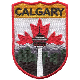 This emblem has the name 'Calgary' at the top on a yellow background. Just below it, front and center, is the Calgary tower. Moving deeper into the background are black and green building silhouettes and then a snow capped mountain. The center portion of Canada's red and white flag peaks out from behind the mountain.