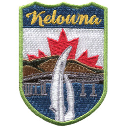 This emblem has the name 'Kelowna' at the top on a blue background. Just below it, front and center, is is a tri-peaked tower. Moving deeper from foreground to background is a lake, a bridge, and brown hills. The center portion of Canada's red and white flag peaks out from behind the mountain.