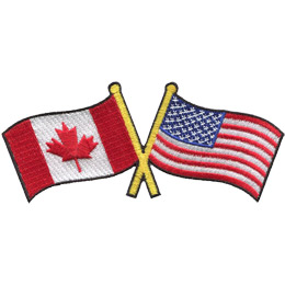 This badge displays the Canadian flag on the left and the United States flag on the right. The flag poles of each flag are crossed with each other, forming a X shape.