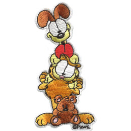 Odie, the dog from the Garfield comics, is standing on top of Garfield, the orange and black striped cat, who has Pooky, the stuffed teddy bear, sitting in front of him.
