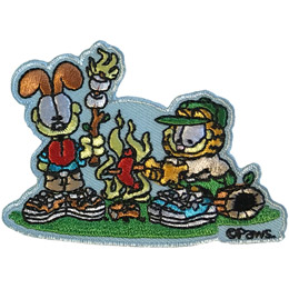 Garfield the cat is dressed in camping shorts, shirt, and cap as he sists on a log and roasts a hotdog over the open flames of a campfire. His pal Odie, the dog, also dressed in a camping shirt, shorts, and shoes, stands on the other side of the fire holding up his flaming marshmallows on a stick.