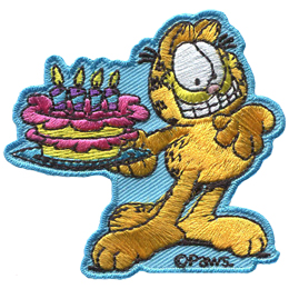 Garfield, the orange and black stripped, overweight house-cat, holds up a double layered yellow cake with pink frosting and four candles on top. The PAWS trademark sits at the bottom of the patch.
