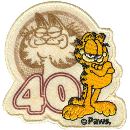 Garfield, the orange and black stripped, overweight house-cat, stands before the faded image of his old self, the original art style of Garfield, and the number 40. The PAWS trademark sits at the bottom right of the patch.