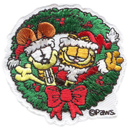 Garfield, the orange and black stripped, overweight house-cat, is dressed in a Santa suit and has his arm wrapped around his buddy Odie, the dog. Odie is wearing a Santa hat. Both of them are sticking out of the center of a Christmas wreath. The PAWS trademark sits at the bottom right of the patch. Odie is on the left and Garfield is on the right.