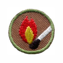 This round one inch badge depicts a lit match.