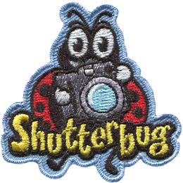 A ladybug holds a camera as if it is about to snap a photo. The word 'Shutterbug' is embroidered under the camera, but overlapping the ladybug's legs.