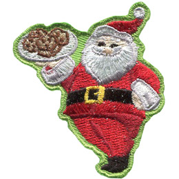 Santa Clause proudly holds up a tray of cookies and gives a big jolly smile.