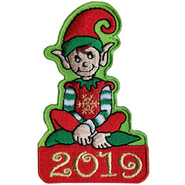 A male Christmas elf sits cross-legged on a red box with 2019 embroidered in metallic threads on it. He wears a red tunic with a gold metallic snowflake on its front, a red and green hat, and green pointed shoes.