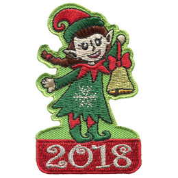 A female Christmas elf dangles a golden bell (made with gold metallic thread) on a ribbon out in front of her. She wears a green dress with a silver metallic snowflake on its front, a red and green hat, and green pointed shoes. This elf stands proudly on top of a red block with the date '2018' embroidered on it in silver metallic.