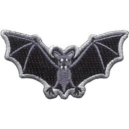 A bat stares at the viewer with beady eyes, pointed fangs, and its wings outstretched.