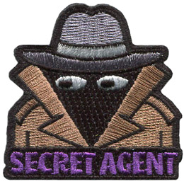 A person is hidden in the shadows of his brown trench coat and wide brim hat. The words 'Secret Agent' are embroidered at the bottom.