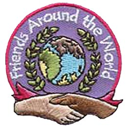 A globe is surrounded by a wreath of leaves which in turn is surrounded by the words ''Friends Around The World.'' Two hands shake at the bottom of the patch.