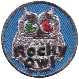 This grey owl looks like a statue with one ruby and one emerald eye. Text near the bottom of the crest says \'Rocky Owl\'.