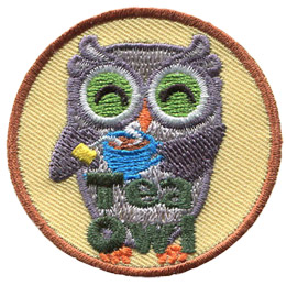 A grey owl smiles and holds a steaming cup of tea with the tea bag still in it. At the bottom of this crest are the words \'Tea Owl\'.