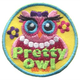 This pretty pink owl has big blue eyes and wears a pearl necklace, a purple bow, and a red gown. A single flower sits in the background on either side of her.