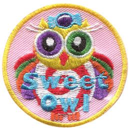 This owl is covered in sweets and a rainbow of colours. On it's head is a purple wrapped candy. It's belly consists of a red and white swirl. The owl's wings are rainbow and it has one purple eye and one green eye.
