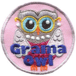An elderly owl is attired in a pink dress, gold-rimmed glasses, pearl earnings, and a pearl necklace. This owl's white wings look like a shall draped over the shoulders. The words 'Grama Owl' are embroidered near the bottom of this round crest.