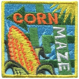 Arrows twist this way and that, confusing in their pattern on this square patch. In the bottom right a cob of corn sticks out and next to it are the words 'Corn Maze.'