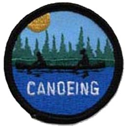 This round badge depicts the silhouette of two people paddling in one canoe along a rippling lake or river. A descending sun is just touching the tips of the trees in the background.