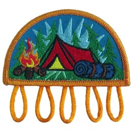 A tent sits in the middle of a treed forest. A roaring campfire rests before the tent at the bottom left of the patch and a bedroll sits at the bottom right. Five loops dangle from the base of this patch for which you can attach charms too.