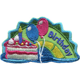 The middle hump of a sea serpent. The word 'Birthday' is embroidered along the right of the hump. A slice of birthday cake with one lit candle rest on the left most section of the hump. Two balloons separate the cake from the word 'Birthday'.
