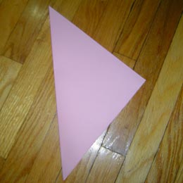<p>Fold the paper in half on the diagonal, corner to corner.</p>