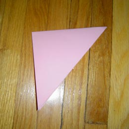 <p>Fold the paper in half once more, corner to corner.</p>