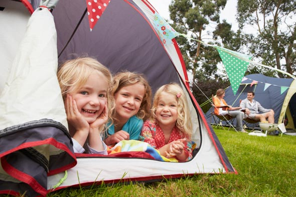 Three girls playing in a tent.