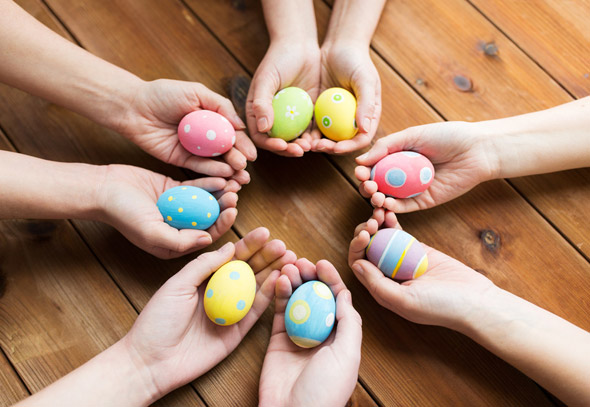 Hands holding colourful easter eggs form a circle